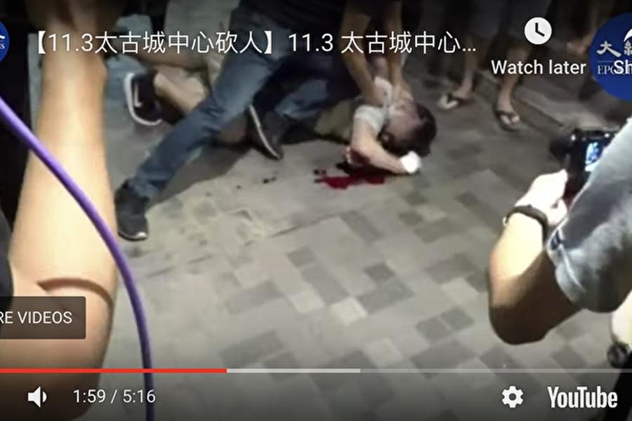 一名說普通話的灰衣男子跟港人發生口角後持刀傷人,至少造成4人受傷,他還咬掉區議員趙家賢的耳朵。(影片截圖)
