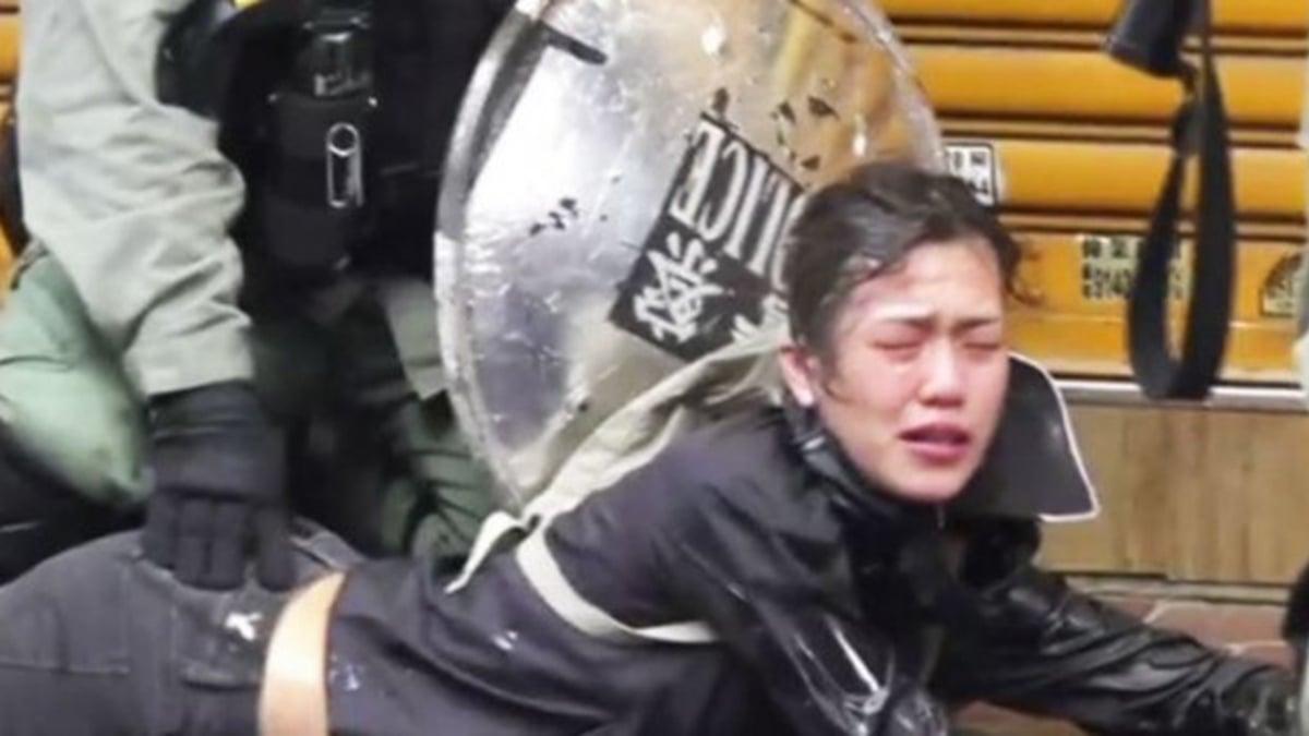 2019年11月2日一名女抗爭者遭警員直接向臉部噴灑胡椒噴霧,並遭壓倒拘捕,而一名警員將手壓在該女的臀部上,引香港網友怒罵。(擷取自立場新聞臉書)