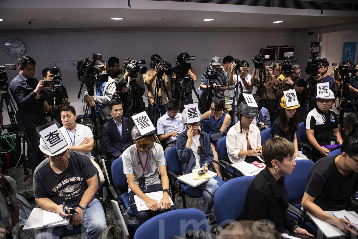11月4日,六名記者戴頭盔,上書「查警暴,止警謊」大字,出席警方例行記者會,抗議近日警察對記者濫暴,妨礙新聞自由,以及編造謊言為其劣跡辯護的行為。(余鋼/大紀元)