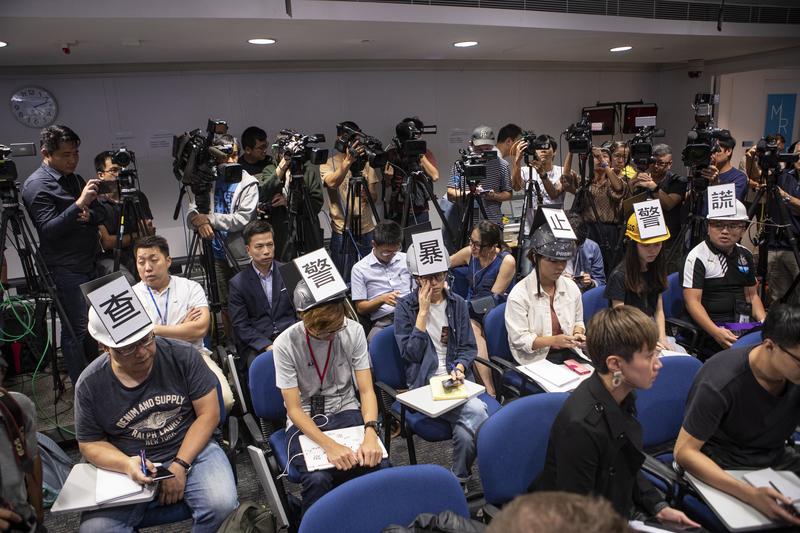 6名記者出席警記者會時,戴上貼有「查警暴 止警謊」標語的頭盔。(余鋼/大紀元)