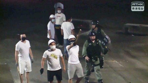 現場記者拍攝的畫面,清楚可見白衣人手持長棍及鐵枝,站在防暴警察身旁。(影片截圖)