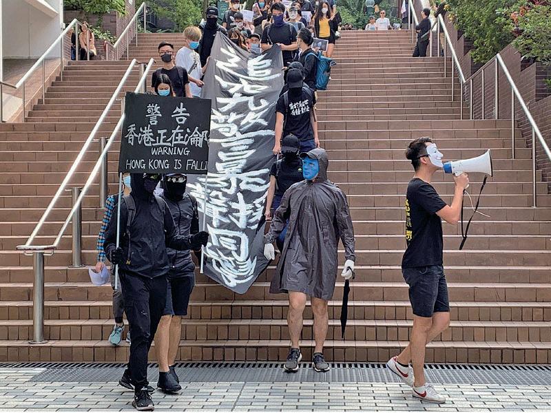 昨日,港大學生在校園內遊行,展示「警告:香港正在淪陷」的黑旗,高喊「香港警察,蓄意謀殺」等口號,要求查明科大學生周同學墮樓真相。(韓納/大紀元)