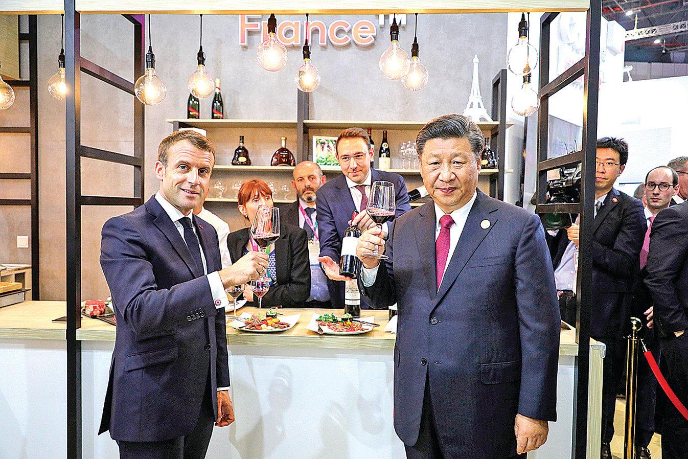 11月5日,第二屆進博會,習近平與馬克龍(左)在進博會法國展位旁,共同品嚐葡萄酒。(AFP)