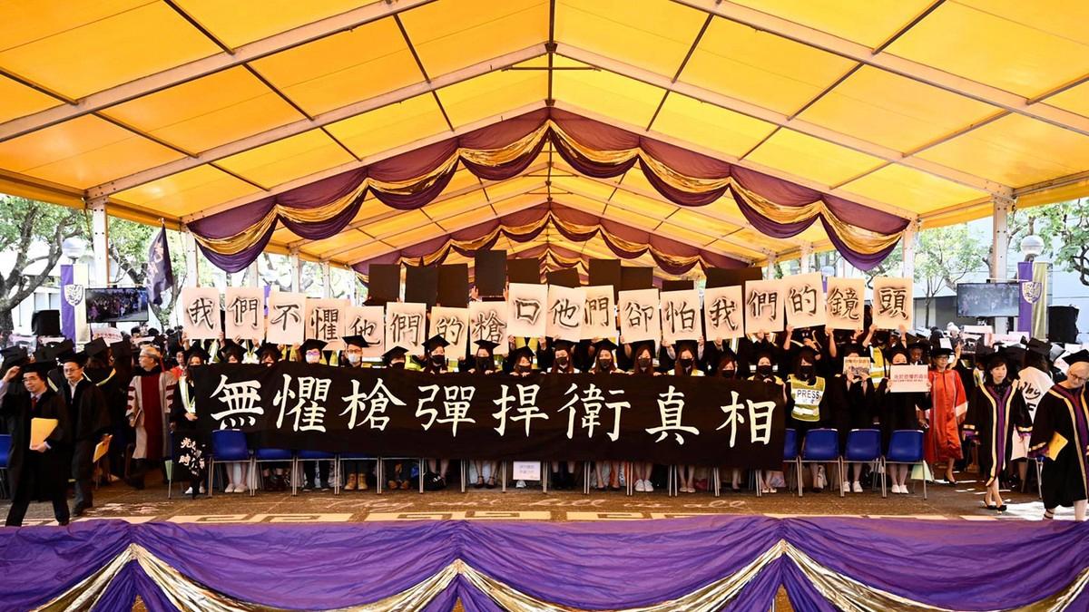 香港中大畢業生舉起寫有「無懼槍彈捍衛真相」、「我們不懼他們的槍口,他們卻怕我們的鏡頭」等標語。(立場新聞圖片)