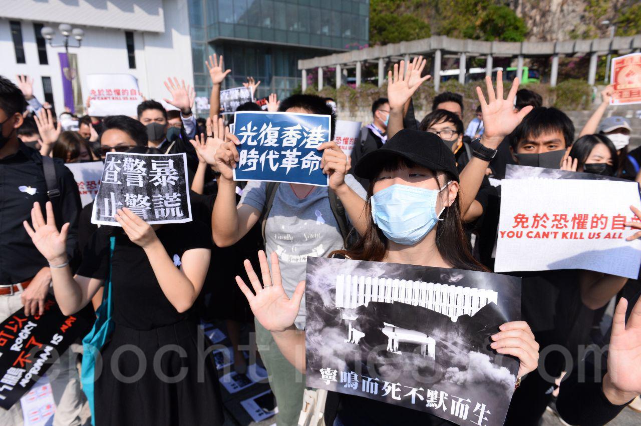 7日中大舉行畢業禮,在校園裡,學生舉起寫有「無懼槍彈 捍衛真相」,「我們不懼他們的槍口 他們卻怕我們的鏡頭」等橫幅聚會。(宋碧龍/大紀元)