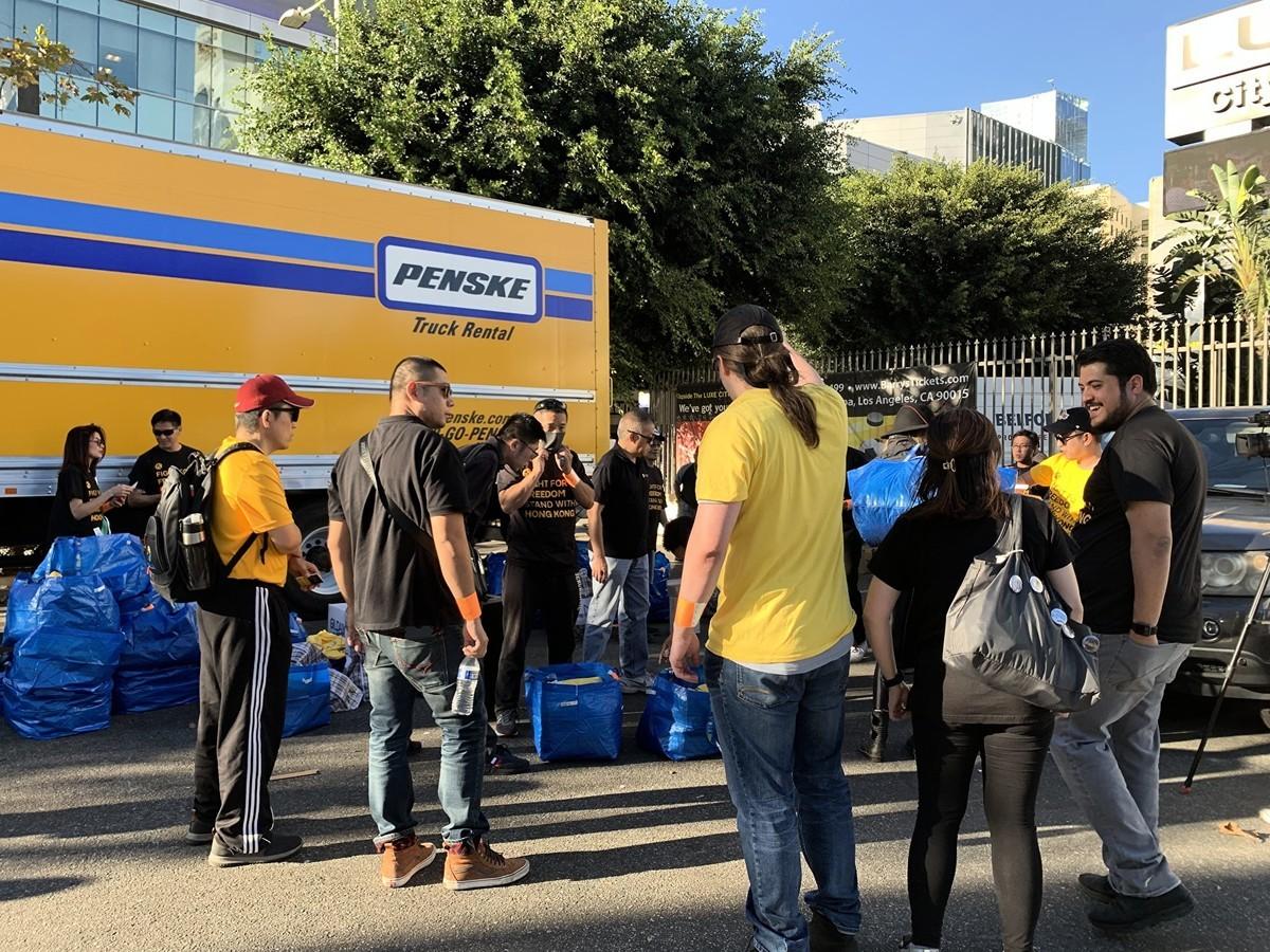 10月22日,在洛杉磯,上百位義工現身湖人隊迎戰快船隊的比賽現場,在場外派發支持香港的黑色T恤。(姜琳達/大紀元)