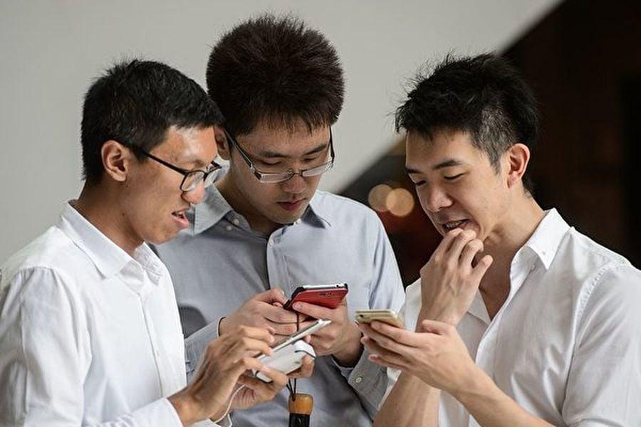 在香港,已經有多個社交平台及應用程式支援用戶搜尋餐館信息了解業者的政治立場,以決定是否消費。示意圖,人們在使用手機。(ANTHONY WALLACE/AFP/Getty Images)
