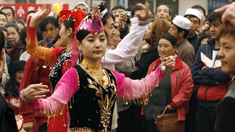 有觀察員披露,中共僱傭臨時演員在街頭表演,等外國遊客走後,這些跳舞的新疆女子就被警車拉走。資料圖(Getty Images)