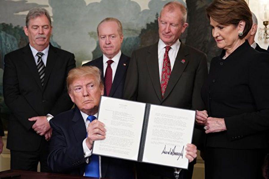 特朗普總統2018年3月22日簽署備忘錄,反制中共竊取美國知識產權。(MANDEL NGAN/AFP/Getty Images)