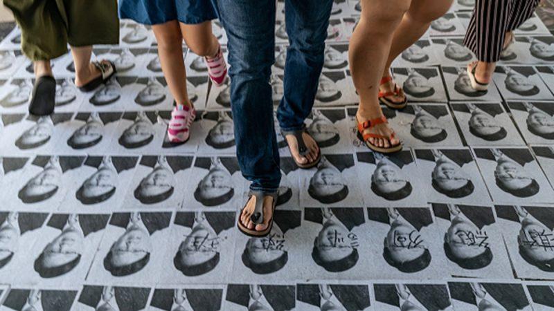 親共議員何君堯在醫院耍特權,遭一位病人家屬怒轟。圖為何君堯的肖像鋪滿天橋地上,被市民怒踩。(Anthony Kwan/Getty Images)