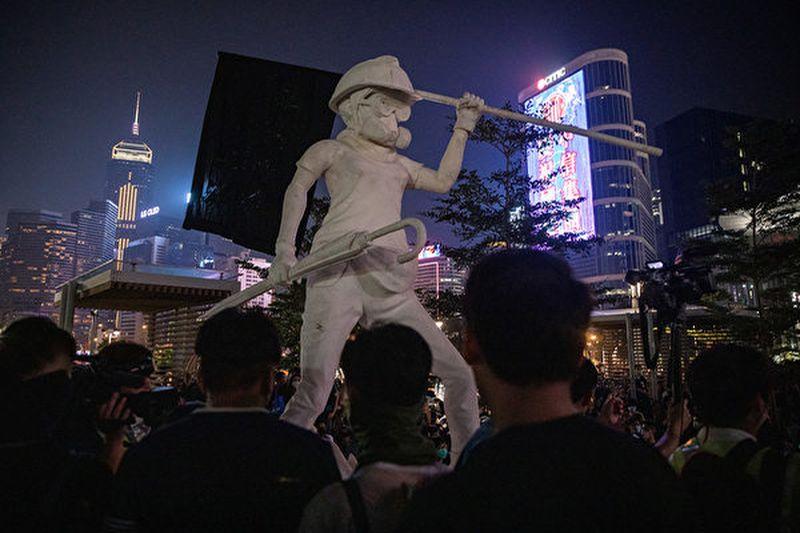 香港《星島日報》和《文匯報》在11月8日刊登頭版廣告,呼籲停止選舉。圖為2019年9月28日,香港民主女神像與反送中抗議者。(Chris McGrath/Getty Images)