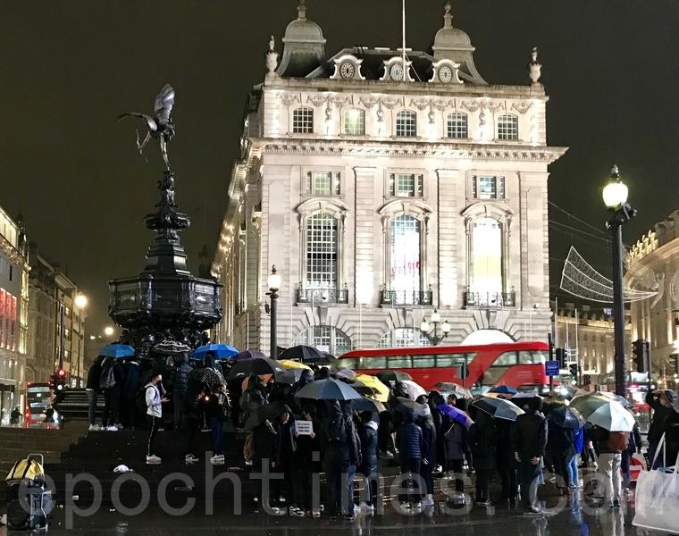 11月8日英國時間晚上八時,近百名港人聚集於倫敦地標Piccadilly Circus,以燭光悼念周梓樂同學並獻上白色鮮花。港人在大雨下聚集燭光前默哀。(唐詩韻/大紀元)