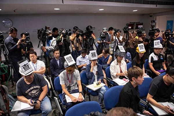 港警的警暴劣蹟日趨嚴重,引社會各界憂慮,11月4日,警方例行記者會有六名記者戴上頭盔展示「查警暴,止警謊」大字,表達對近日警察濫暴的不滿。(余鋼/大紀元)
