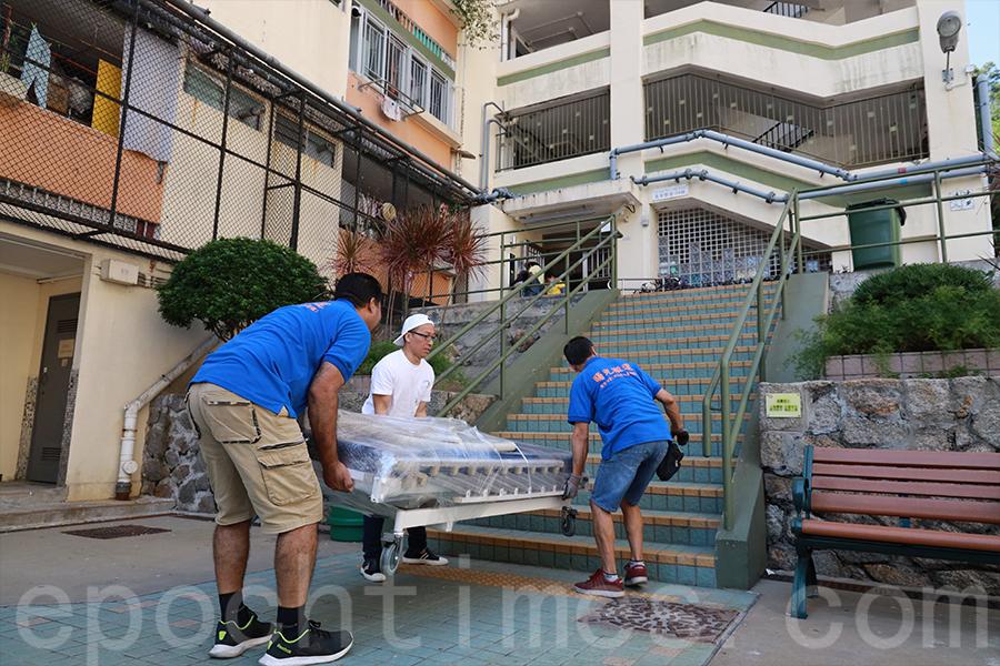 「曙光搬運」團隊將76公斤重的醫療床抬上階梯。(陳仲明/大紀元)