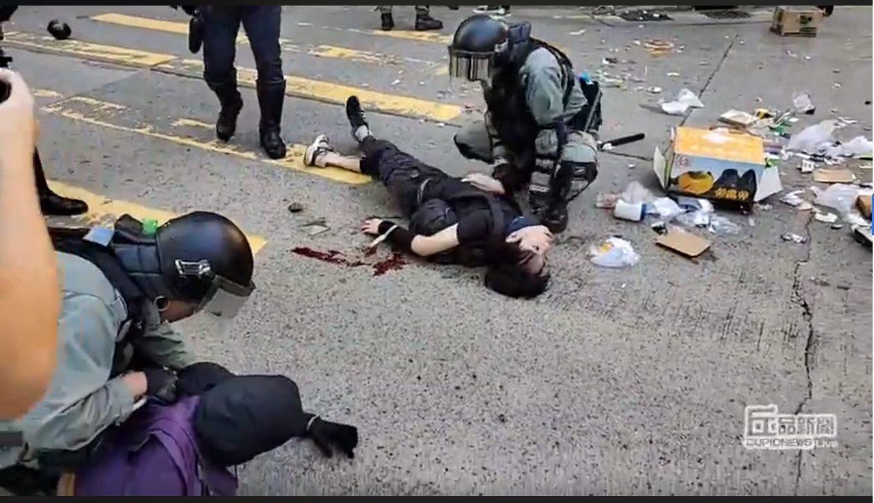 一名警員在太安樓對開向一名黑衣人士,現場遺下大灘血跡。(網絡圖片)