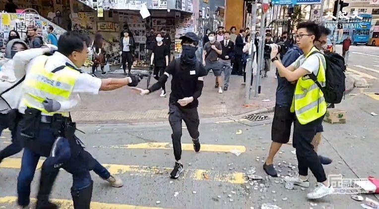 11月11日早上,香港警察至少以3發實彈射向民眾,其中一名手無寸鐵的黑衣人腹部中槍倒地。(影片截圖)