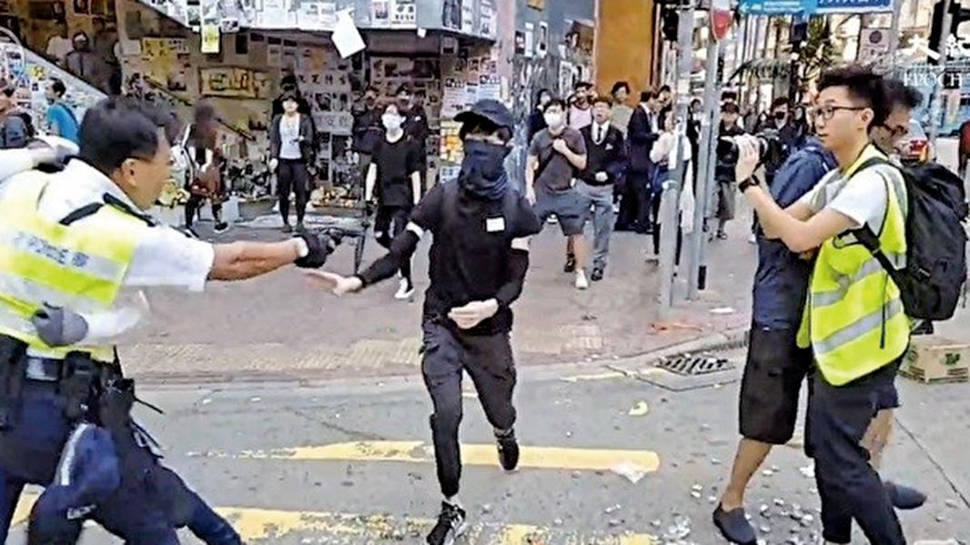 在西灣河警員關家榮向手無寸鐵示威者開3槍造成2人流血倒地。(影片截圖)