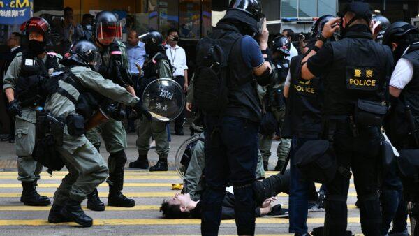 香港民眾11日發起「三罷」行動,港警以真槍實彈射傷示威者,同時在全港濫射噴霧劑,槍指市民大肆抓人揮棍毆狂示威者。( ANTHONY WALLACE/AFP via Getty Images)