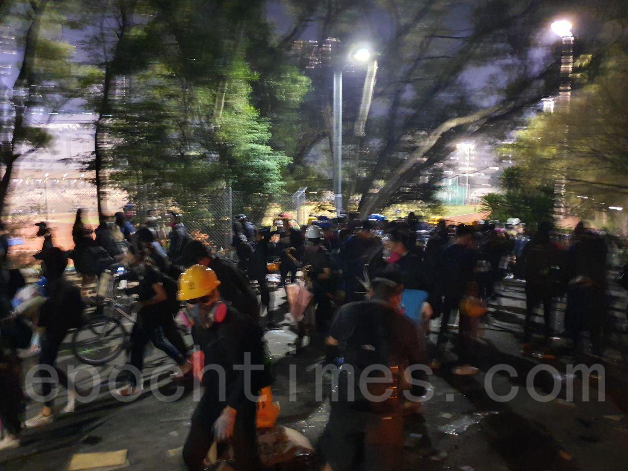 12日,進入晚間,防暴警向中大發動更猛烈攻勢,學生與防暴警長時間對峙。(孫明國/大紀元)