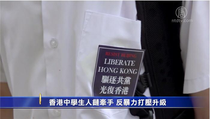 2019年11月12日上百名學生手牽手築成人鏈,大部份人戴口罩,校服的校徽用「驅逐共黨光復香港」標語蓋住,高呼「五大訴求、缺一不可」等口號。(新唐人影片截圖)