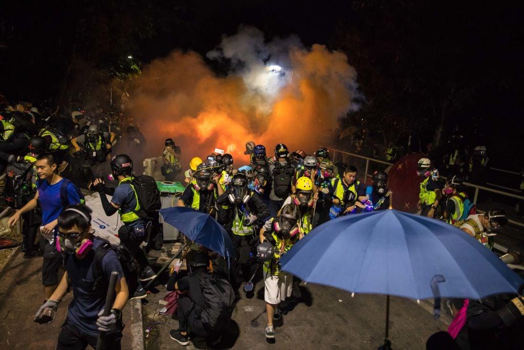 香港警方於2019年11月12日在香港中文大學(CUHK)發射催淚彈後,抗議者(前左)和新聞記者做出躲避反應。(DALE DE LA REY/AFP via Getty Images)