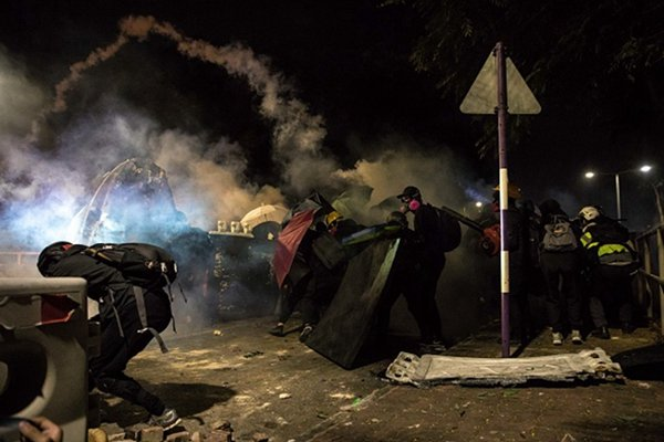 11月12日晚,大批防暴警察強攻中文大學校園,無間斷狂射催淚彈,現場硝煙瀰漫形同戰場。(DALE DE LA REY/AFP via Getty Images)