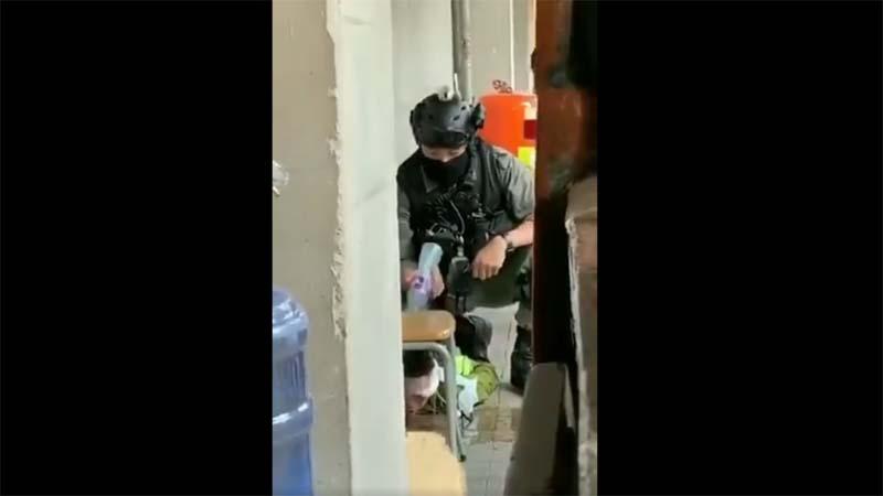 網傳影片顯示,一名香港警察多次用冷水澆在被捕者疑似受傷的頭部。(影片截圖)
