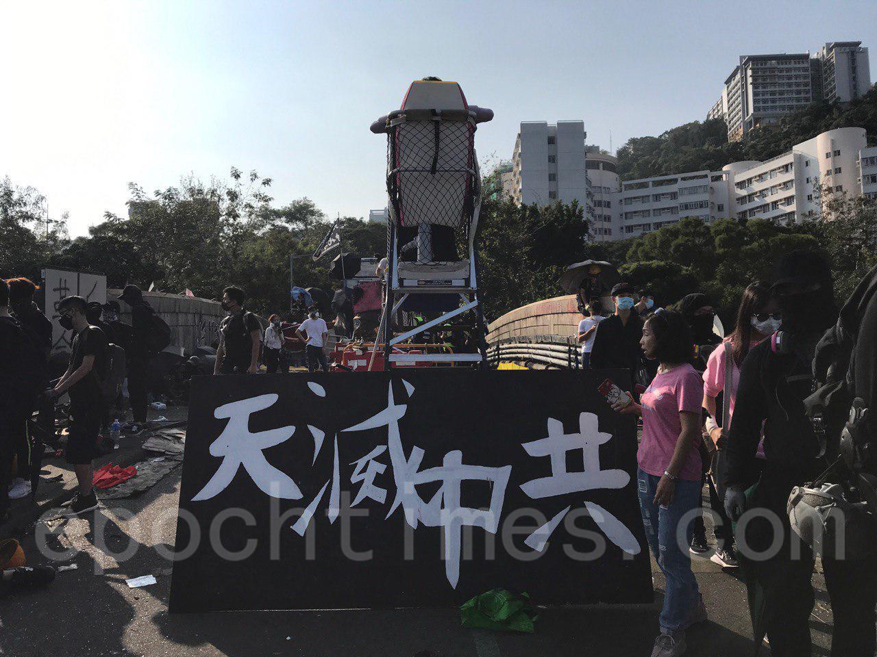 13日,中大學生警惕警察再度強攻校園,在二號橋築路障,並在陣地上豎起「天滅中共」橫幅。(余鋼/大紀元)