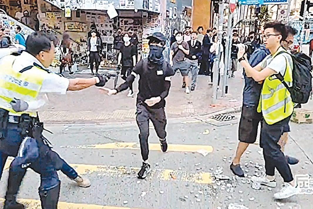 11月11日,香港警察關家榮向手無寸鐵的抗議者開槍,抗議者被擊中腹部。(影片截圖)