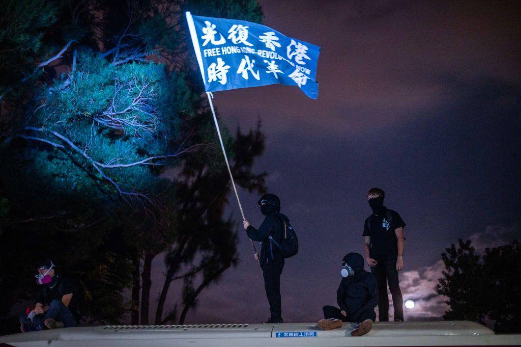11月12日,在香港中大,防暴警察瘋狂發射催淚彈,學生統計,發現有2000多發彈殼。圖為抗爭者舉著「光復香港 時代革命」的旗子。(Getty Images)