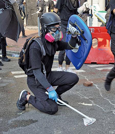 被槍擊前,「健仔」曾志健被拍到手持的是白色塑膠短棒。(JASMINE LEUNG/AFP via Getty Images)