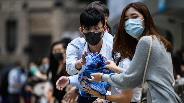 市民們組成人鏈傳送抗爭物質。(ANTHONY WALLACE/AFP via Getty Images)