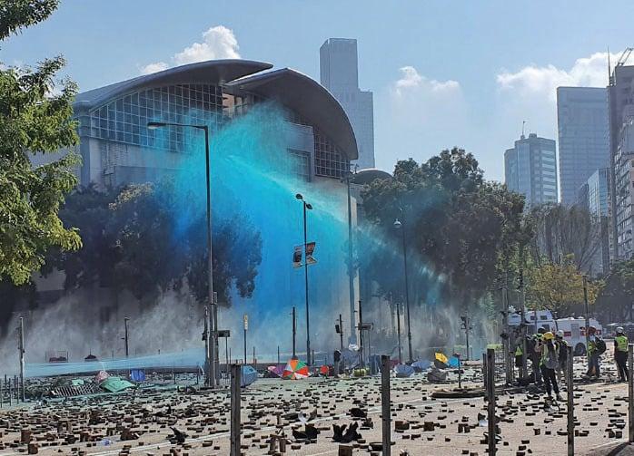 警方水炮車多次向理大方向發射藍色及白色化學水劑,理大平台及漆咸道南的路面染上藍色,路上留下一灘灘藍色水。(孫明國/大紀元)