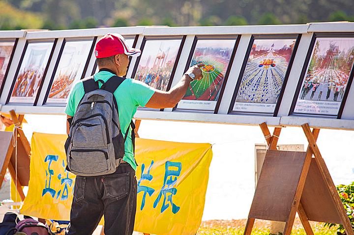 遊客駐足觀賞法輪大法正法之路圖片展。(陳柏州/大紀元)