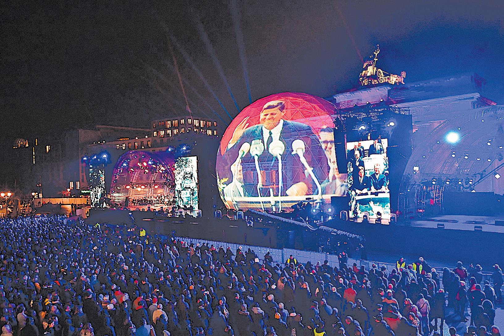 11月9日晚,十萬多觀眾參加了柏林市中心地標勃蘭登堡門前的慶祝活動,把紀念柏林牆倒塌30周年系列慶典推向高潮。圖為晚會上,大型屏幕打出了當年美國總統甘迺迪在西柏林演講的畫面,他的名句「我是柏林人」,鼓舞著當時被柏林牆圍困的柏林人堅持自由民主價值。(TOBIAS SCHWARZ/AFP/Getty Images)