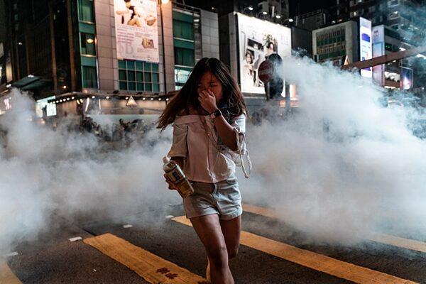 一名女生在催淚彈濃煙中奔逃。(Anthony Kwan/Getty Images)