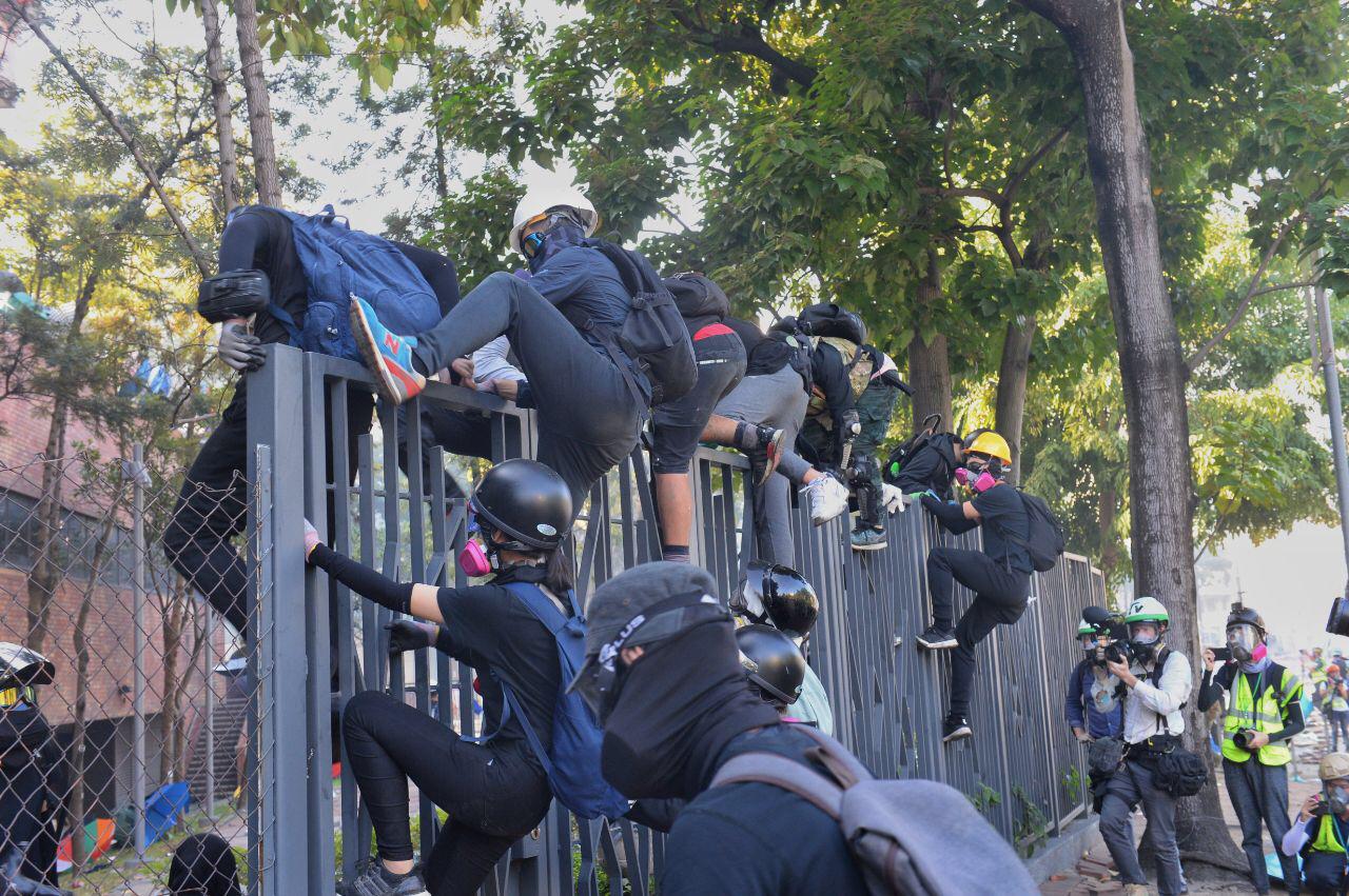 18日,理大內的抗爭者和學生逃跑遇警,再折回校園。(宋碧龍/大紀元)
