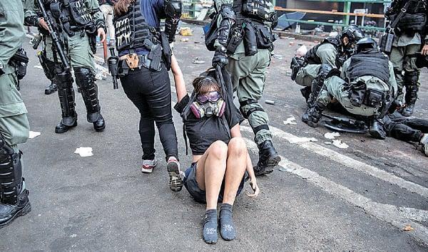 暴警粗暴對待被捕抗爭者及學生,用腳踩他們的頭或頸、用拳頭或警棍毆打、拖行已失知覺抗爭者致褲子也扯脫等。圖中女子已遺失鞋子,仍被拖行。(Laurel Chor/Getty Images)
