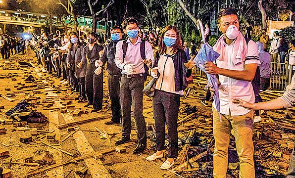 昨晚大批聲援被困理大生的市民,在校園一帶主要馬路與防暴警對峙,並組成人鏈運送物資。(DALE DE LA REY/AFP via Getty Images)
