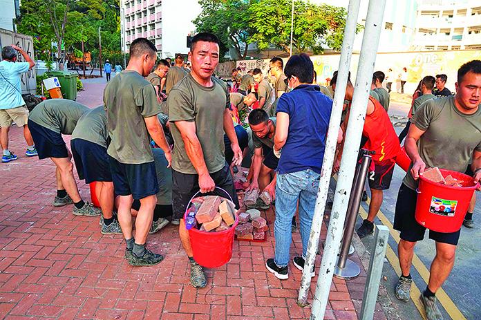 11月16日下午,中共駐港部隊沒有得到港府的請求就突然跑出軍營,清理反送中抗議者設下的磚頭、鐵柵欄等路障。(影片截圖)