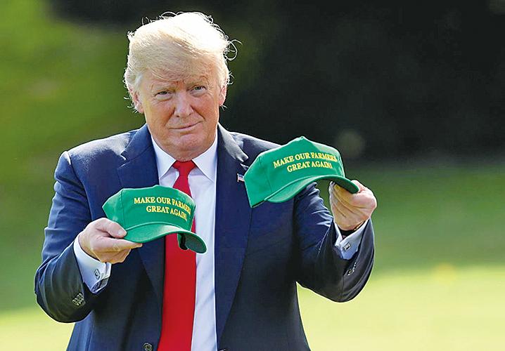 美國總統特朗普2018年8月30日,在白宮準備前往印第安納州前秀出兩頂繡著「讓我們的農民再次偉大!」的帽子。(Getty Images)