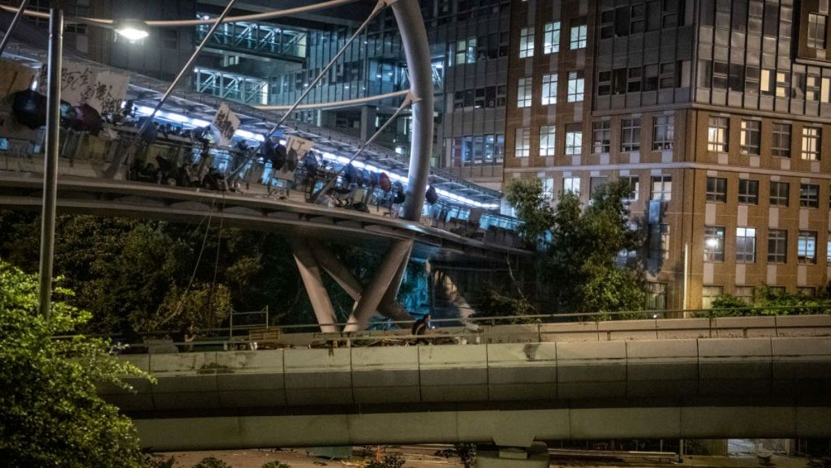 2019年11月18日香港理工大學的部份抗爭者被警方重重包圍後,靠繩索從人行天橋垂降到公路逃離香港理工大學校園。(Laurel Chor/Getty Images)