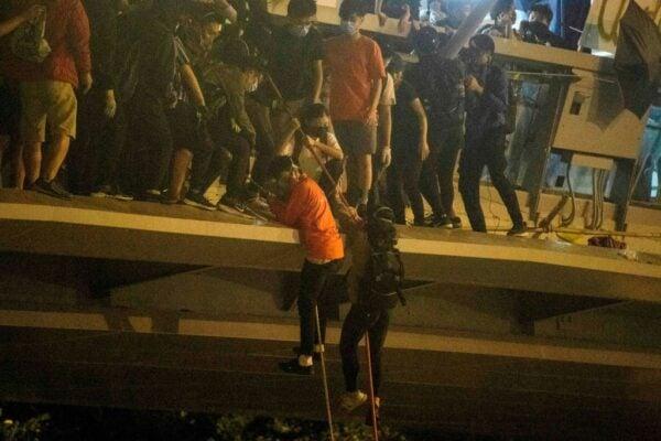 香港理工大學的部份抗爭者2019年11月18日被警方重重包圍後,靠繩索從人行天橋垂降到公路逃離香港理工大學校園。(ANTHONY WALLACE/AFP via Getty Images)