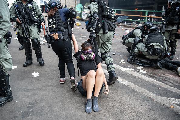 女生被港警在地上拖行,鞋子被拖掉,襪子也快磨穿。(Laurel Chor/Getty Images)