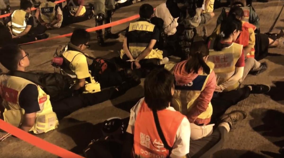 11月17日在理大的義務護理及現場記者,聽信警方說10點前疏散可自行離開,全部被捕。(影片截圖)