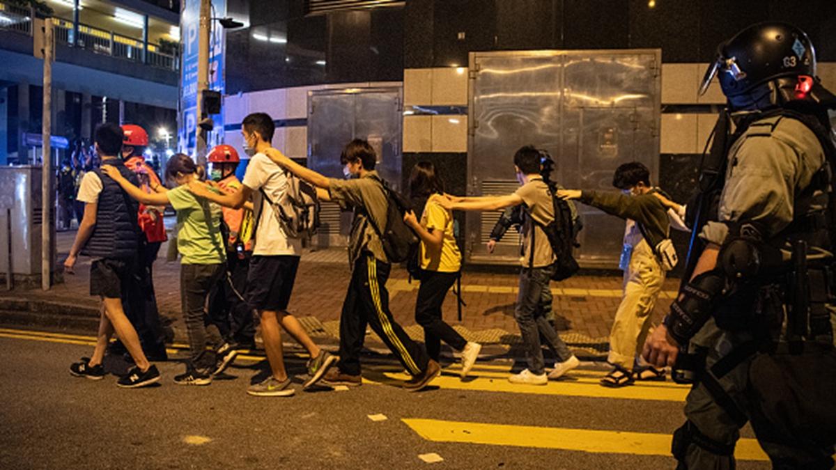 一群被抓捕的抗爭者被持槍港警押著往前走。(Laurel Chor/Getty Images)