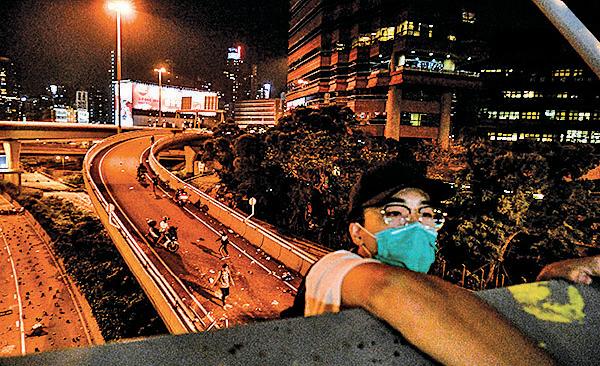 被困理大抗爭者及學生由天橋游繩而下逃走,過程十分驚險。(ANTHONY WALLACE/AFP via Getty Images)
