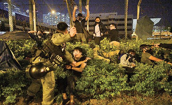 一批被困理大抗爭者及學生昨晚嘗試逃走,遭暴警暴力阻截。(NICOLAS ASFOURI/AFP via Getty Images)