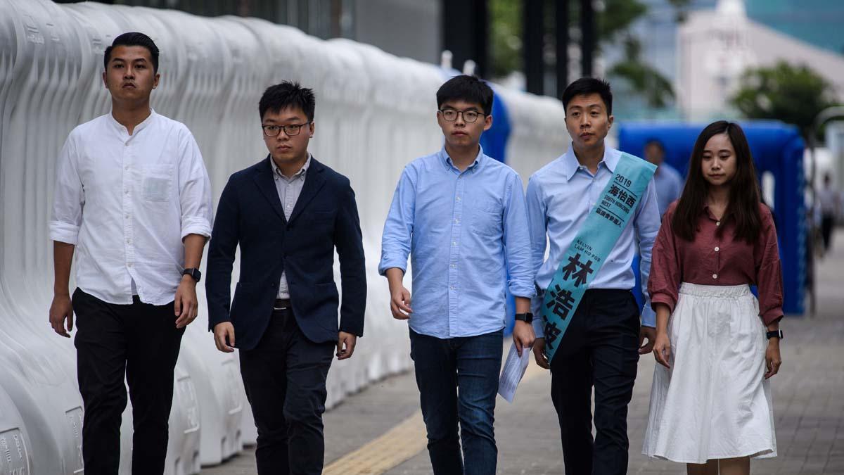 香港區議會選舉前,黃之鋒(中)被取消候選人資格,另有多名民主派候選人被抓被打。 (ANTHONY WALLACE/AFP via Getty Images)