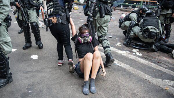 一名走出理大校園的女性抗爭者直接被警察在地上拖行帶走。(Laurel Chor/Getty Images)